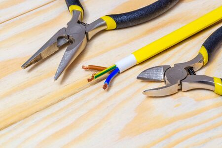 Pliers and cable on wooden boards laid out by craftsman before work