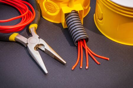 Spare parts, tools and wires for replacement or repair of electrical equipment on black background