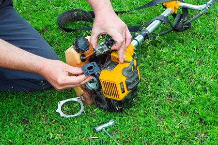 Worker repairs a carburetor in trimmer or lawn mower that lies on the grass
