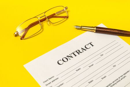 Contract form on the yellow office desk with glasses and pen