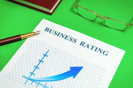 Business rating chart on the green office desk with notebook and stylish pen, business idea