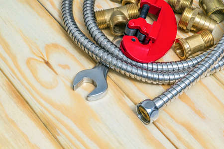 Plumbing materials, tools, fittings and hose on wooden boards used to replace or repair
