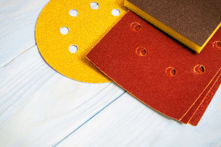 Set of abrasive tools and brownyellow sandpaper on wooden blue boards