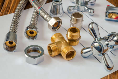 Spare parts with copper and plastic accessories for plumbing repair on note sheet