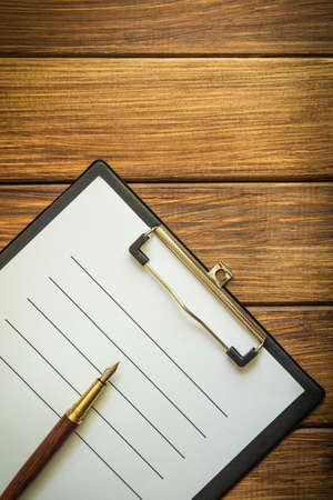 Paper sheet with empty to do list and a pen on vintage wooden table