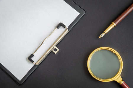 Magnifying glass and paper sheet with empty to do list and pen on black background 版權商用圖片