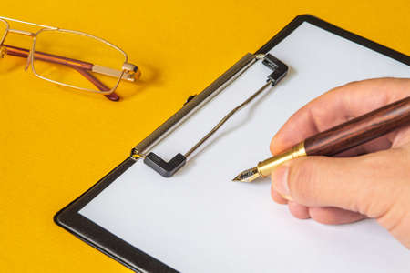 The hand holds a stylish pen for writing text on blank sheet of paper