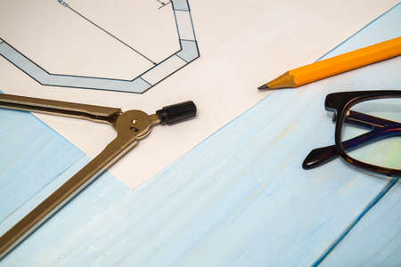 House diagrams and accessories for drawing lying on construction drawing and a blue table for projects engineer jobs