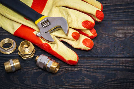 Brass fittings and yellow work gloves on vintage boards. The working environment of master plumber