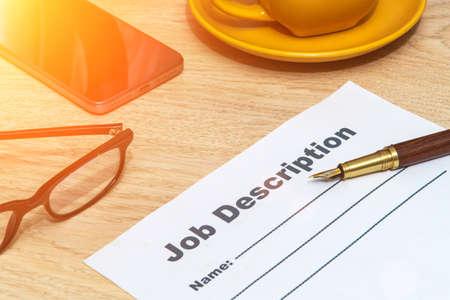 Job description form on office desk with elegant pen and smartphone. Business idea.