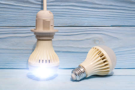 Two energy saving light bulbs with a glowing other on a background of blue boards