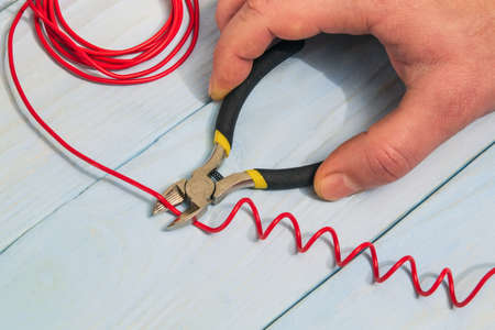 The master electrician cuts the red wire with diagonal cutting pliers. Electronics Repair Idea