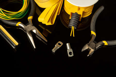 Set of spare parts and tools for repairing an electrician on a black isolated background. Workplace of master electrician
