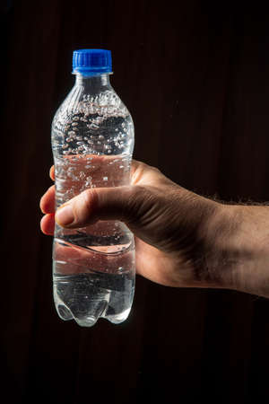 Person hand holds a bottle of mineral water to quench thirst. Vertical image on a dark background