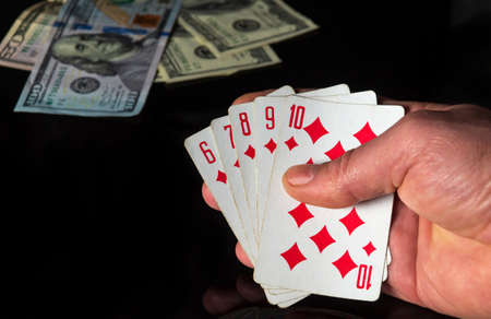 Poker cards with a straight flush combination. Close up of a gambler hand is holding playing cards in casino