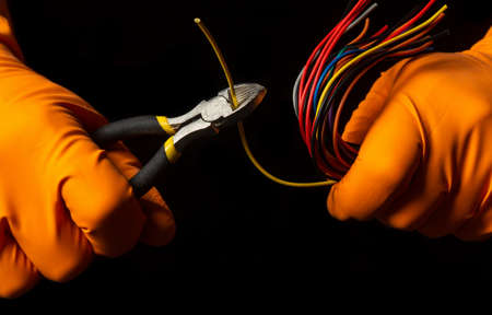 Hands of the master in gloves hold wire cutters and wire closeup on black background. Electronics Repair Idea Stock Photo