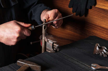 The master grinds the part with a file in a vice. Working environment in the workshop