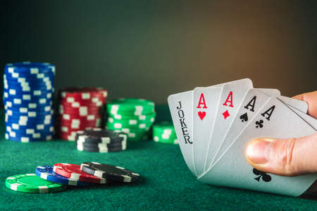 Poker cards with five of a kind combination. This is the maximum win. Close up of gambler hand takes playing cards in poker club