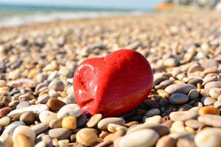 valentine s day beach: red heart of stone among the stones on the sea beach