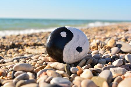 Symbole yin yang peint sur un rocher sur la plage de la mer Banque d'images - 66161630