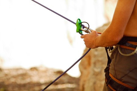 belay: male belayer with the rope and carabines Stock Photo