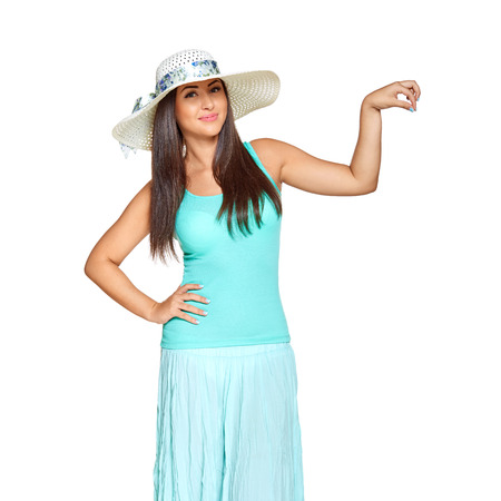 suntanned: young sun-tanned woman  dressed in a turquoise shirt and a straw hat shows that holding something in her hand and smiling at the camera, isolated on white background