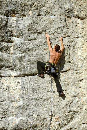 lead rope: Young man climbs on a rocky wall
