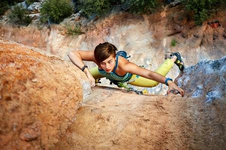 high mountain: female rock climber climbs on a rocky wall