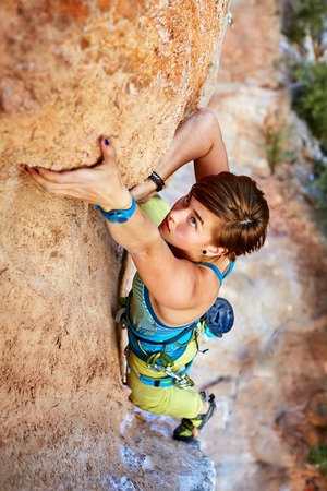 Femme grimpeur grimpe sur un mur rocheux Banque d'images - 34890471
