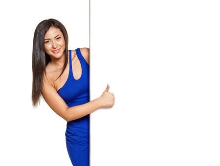 smiley pouce: Jolie femme smiley furtivement par derri�re le walll, portant robe bleue �troite, gaine. Afficher Thumb up. Isol� sur blanc Banque d'images