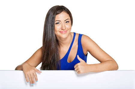 sheath: Pretty smiley woman peeking out from behind the walll, wearing   blue narrow dress, sheath. Showing Thumb UP. Isolated on white Stock Photo