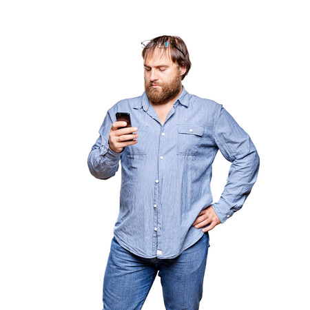 big shirt: fat man wearing jeans and blue shirt looking at smartphone, isolated on a white background