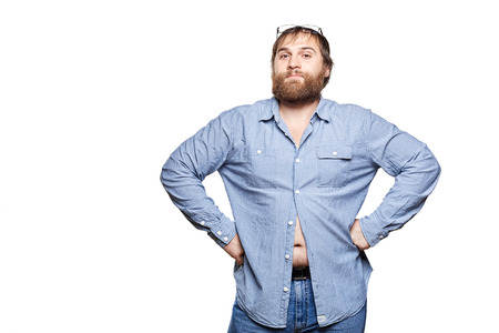 fat man with glasses wearing jeans and blue shirt, with hands on hips  looking at camera, isolated on a white background
