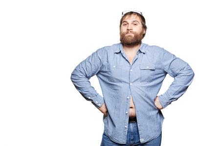 hombre gordo con gafas con pantalones vaqueros y camisa azul, con las manos en las caderas mirando a la cámara, aislado en un fondo blanco