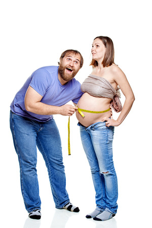 stout man with measure tape and pregnant woman on a white background, isolated on a white background photo
