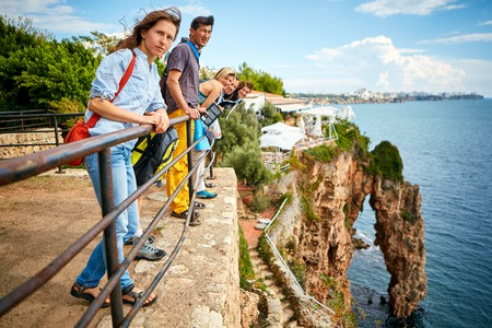 rock arch: Tourists on a viewing platform with rock arch on background Stock Photo