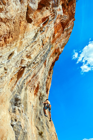 male rock climber climbs on a rocky wall Stock Photo