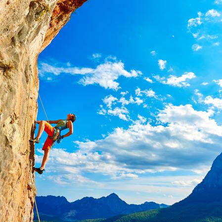 female rock climber climbs on a rocky wall