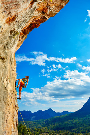 cliff top: female rock climber climbs on a rocky wall