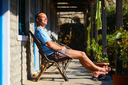man relaxed and enjoy in chair at the sunny morning in patio Stock Photo