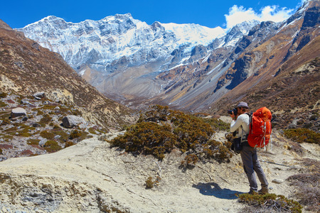 Hiking photographer taking pictures. Trek around Annapurna mount. Stock Photo