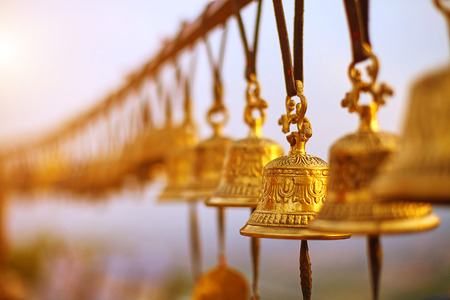 Nepaly traditional Bells over the sun at sunset photo