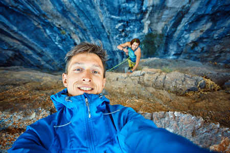 young  man make selfie on the rock background