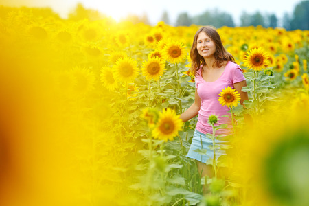 Happy woman in sunflower field. Summer girl in flower field cheerful and joyful. Stock Photo