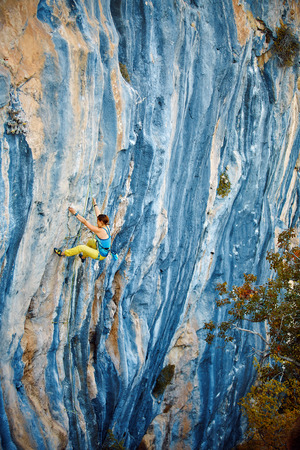 female rock climber climbs on a rocky wall. Cidtibi Canyon, Geyikbayiri, Turkey. Stock Photo