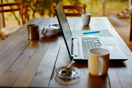 access: Laptop computer, phone and coffee in the garden - freelance or remote work concept. small depth of field, focus on the keyboard Stock Photo