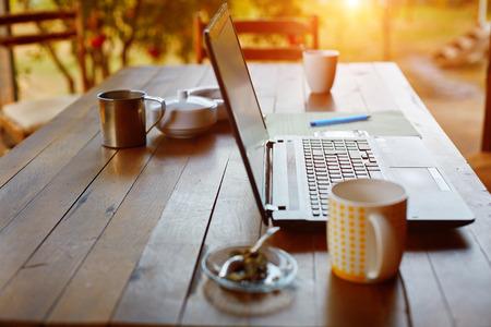 klawiatura: Laptop, telefon i kawy w ogrodzie - niezależny lub zdalne koncepcja pracy. mała głębia ostrości, koncentrują się na klawiaturze