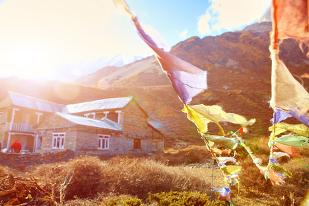 venerable: Hotel in mountains and traditional flags with prayer on the foreground.   Trek around Annapurna mount. Tilicho lake region. Nepal