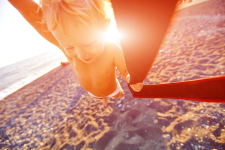 turns: someone turns a little girl on the beach at sunset Stock Photo