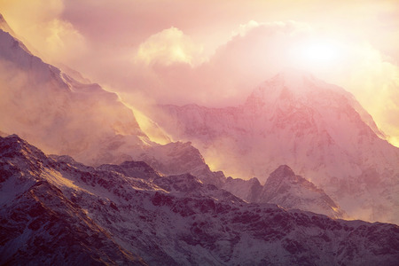 beautifull cloudy sunrise in the mountains with snow ridge. Trek around Annapurna mount. Himalaya, Nepal. Stock Photo